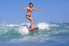 Muchacha de la persona que practica surf en onda azul asombrosa Fotos de archivo