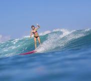 Muchacha de la persona que practica surf en onda azul asombrosa Fotografía de archivo