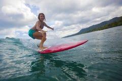 Muchacha de la persona que practica surf en onda azul asombrosa Imagen de archivo libre de regalías