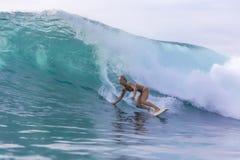 Muchacha de la persona que practica surf en una onda Fotografía de archivo libre de regalías