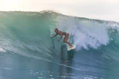 Muchacha de la persona que practica surf en una onda Imagen de archivo