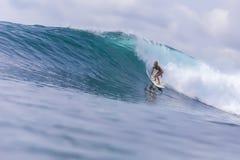 Muchacha de la persona que practica surf en una onda Imágenes de archivo libres de regalías