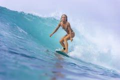 Muchacha de la persona que practica surf en una onda Imagen de archivo libre de regalías