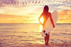 Muchacha de la persona que practica surf que practica surf mirando puesta del sol de la playa del océano Fotografía de archivo libre de regalías