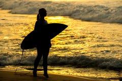 Muchacha de la persona que practica surf que practica surf mirando puesta del sol de la playa del océano Silueta w Imagenes de archivo