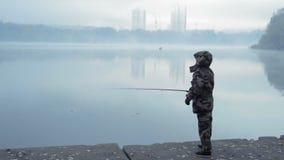 Muchacha de la pescadora en caña de pescar de los tiros del traje del camuflaje en el río en una mañana de niebla del otoño almacen de metraje de vídeo