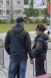 Muchacha de la policía que habla en la calle con los hombres fotografía de archivo