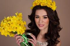 Muchacha de la primavera con el ramo de flores del narciso Imagen de archivo