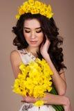 Muchacha de la primavera con el ramo de narcisos amarillos Imagen de archivo libre de regalías