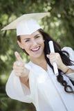 Muchacha de la raza mezclada en casquillo y vestido con el diploma Imagen de archivo