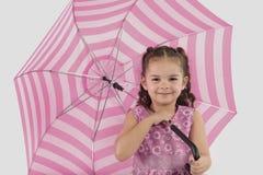 Muchacha de la raza mixta que sostiene el paraguas grande, rosado fotografía de archivo