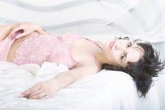 Muchacha de la relajación en la cama. Imagen de archivo