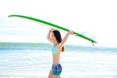 Muchacha de la resaca con la tabla hawaiana en orilla de la playa Foto de archivo libre de regalías