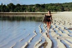 Muchacha de la resaca con la tabla hawaiana en la playa foto de archivo libre de regalías