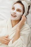Muchacha de la risa con la máscara poner crema que habla en un teléfono móvil Imagen de archivo