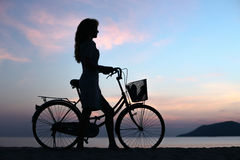 Muchacha de la silueta con la bicicleta Fotos de archivo