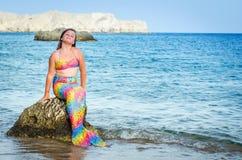 Muchacha de la sirena que presenta en la roca de la playa Fotografía de archivo
