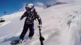 Muchacha de la snowboard en polvo en las montañas que llevan el casco metrajes