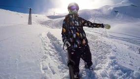 Muchacha de la snowboard en polvo en las montañas que llevan el casco almacen de video