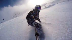 Muchacha de la snowboard en polvo en las montañas que llevan el casco almacen de metraje de vídeo