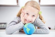 Muchacha de la sonrisa con el globo de la tierra Fotos de archivo libres de regalías