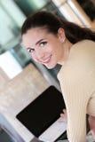 Muchacha de la sonrisa que se sienta en la barra con el ordenador portátil Foto de archivo
