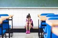 Muchacha de la tensión que se sienta en el piso de la sala de clase Fotos de archivo