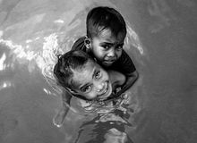 Muchacha de la tribu de Bajau que lleva a su pequeño hermano en su hombro y que juega en el agua, Semporna, Malasia fotografía de archivo libre de regalías
