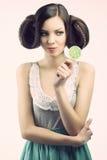 Muchacha de la vendimia con el lollipop, ella mira el lollipop Fotos de archivo
