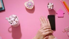 Muchacha de la visión superior que pone la crema de la mano en sus palmas en rosa metrajes