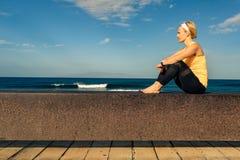Muchacha de la yoga que medita y que se relaja en la actitud de la yoga, vista al mar fotos de archivo
