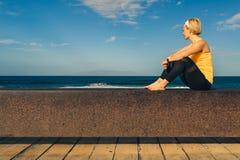 Muchacha de la yoga que medita y que se relaja en la actitud de la yoga, vista al mar imágenes de archivo libres de regalías