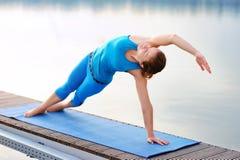 Muchacha de la yoga que practica el tablón lateral que postula en la orilla del río en th Imagen de archivo