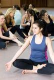 Muchacha de la yogui que se sienta en postura del loto en clase Foto de archivo libre de regalías