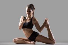 Muchacha de la yogui que usa smartphone Imagenes de archivo