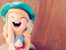 Muchacha de las muñecas de la arcilla que sonríe y que ríe en fondo de madera Imagen de archivo libre de regalías
