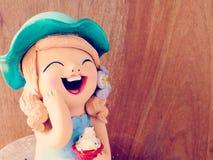 Muchacha de las muñecas de la arcilla que sonríe y que ríe en fondo de madera Imagenes de archivo