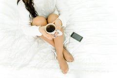 Muchacha de las piernas en la cama con una taza de café Imagen de archivo libre de regalías