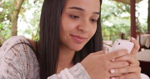 Muchacha de Latina que manda un SMS en smartphone en restaurante Fotografía de archivo libre de regalías