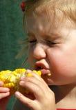 Muchacha de Litle que come el maíz en la mazorca Foto de archivo