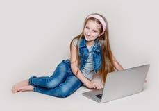 Muchacha de Litlle que miente en piso con el ordenador portátil Fotografía de archivo