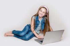 Muchacha de Litlle que miente en piso con el ordenador portátil Fotos de archivo libres de regalías