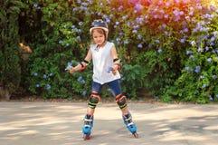 Muchacha de Littl en pcteres de ruedas en casco en el parque, en las manos Imagen de archivo