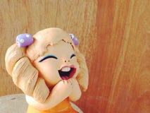 Muchacha de los niños de las muñecas de la arcilla que sonríe y que ríe en fondo de madera Fotografía de archivo