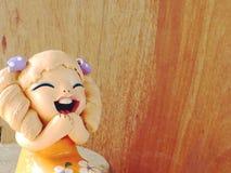 Muchacha de los niños de las muñecas de la arcilla que sonríe y que ríe en fondo de madera Imagen de archivo libre de regalías
