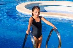 Muchacha de los niños en el traje de baño negro de las escaleras azules de la piscina Foto de archivo