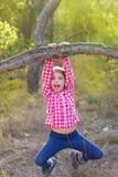 Muchacha de los niños que hace pivotar en un tronco en bosque del pino Foto de archivo