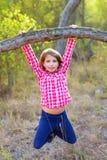 Muchacha de los niños que hace pivotar en un tronco en bosque del pino Imagenes de archivo