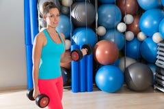 Muchacha de los ojos azules en las pesas de gimnasia del levantamiento de pesas del gimnasio Imagenes de archivo
