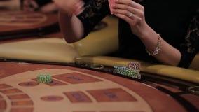 Muchacha de lujo elegante en el vestido negro que juega en el casino La muchacha hace una apuesta almacen de video